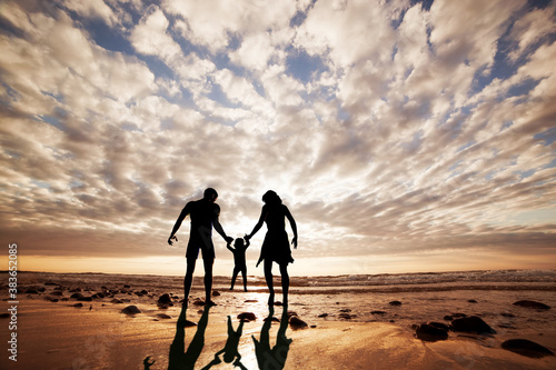 Happy family together hand in hand on the beach at sunset. Summer time, parents, child