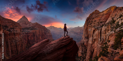 Adventurous Woman at the edge of a cliff is looking at a beautiful landscape view in the Canyon during a vibrant sunset Fototapeta