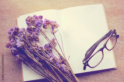 Blank notebook and dried statice flowers with eyeglasses, retro