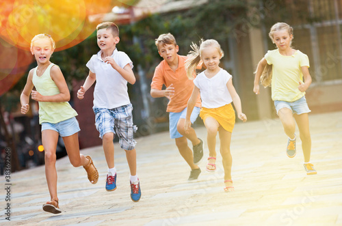 Tela Group of smiling glad children running outdoors in city street on good weather