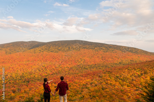 Back view of a young couple admiring the autumnal colours in the Mont-Megantic n Wallpaper Mural