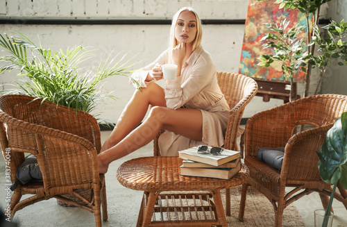 Fototapeta Luxurious hotel room in sunshine with styled bamboo furniture and its female graceful owner in white robe which drinking a tea on chair. obraz