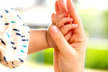 母親と赤ちゃんが手を...