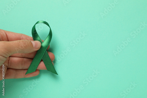 Photo Female hand hold green awareness ribbon on mint background