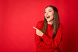 Leinwandbild Motiv Photo of cheerful girl point index finger empty space for ads promo laugh wear jumper isolated over red shine color background