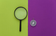 Minimalism Travel, Adventure Flat Lay. Compass And Magnifier On Purple Green Background. Top View