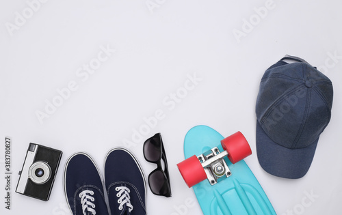 Fotomural Flat lay composition of mini cruiser board, sneakers, cap, sunglasses and camera on white background