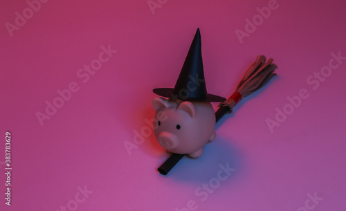 Piggy bank in a witch's hat on a broomstick. Red-blue gradient neon light. Halloween theme