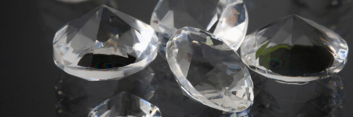 Precious expensive stones lie on black background. Sale of diamonds and polished diamonds creation of jewelry concept