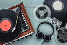 Retro Vinyl Record Player With Records, Audio Magnetic Reel, Audio Cassette And Stereo Headphones On Blue Wooden Background. Top View. Flat Lay