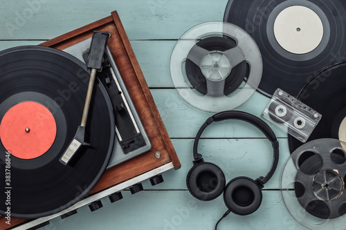 Fototapeta Retro vinyl record player with records, audio magnetic reel, audio cassette and stereo headphones on blue wooden background