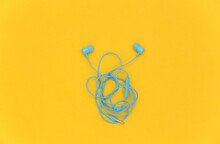 Wired Tangled Headphones On Yellow Background. Top View. Flat Lay