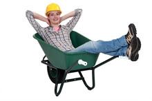 Woman Laborer Resting In A Wheelbarrow