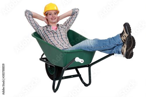 Foto Woman laborer resting in a wheelbarrow