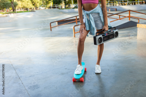 Cuadros en Lienzo Image of young stylish woman skater with cruiser board and retro boombox tape re