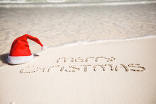 Merry Christmas Written On Tropical Beach White Sand With Xmas Hat