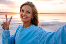 Young Woman Smiling And Gesturing Peace Sign Taking Selfie Outdoors