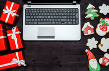 Open Laptop Computer, Christmas Presents And Gingerbread Cookies On Dark Wood Background, Copy Space. Top View, Flat Lay. Santa, Snowflake, Mitten, House, Stocking, Snowman, Fir Tree