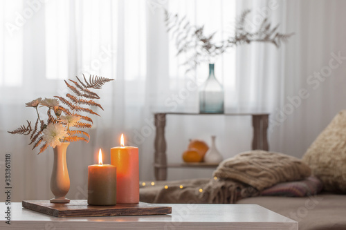 Obraz burning candles with autumn decor on white table at home - fototapety do salonu