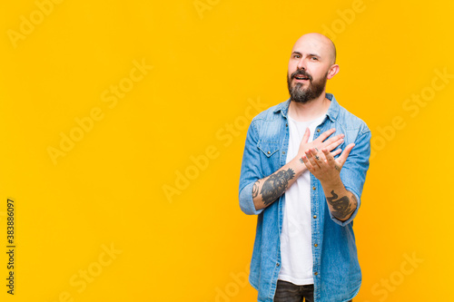 Fotografie, Obraz young bald and bearded man feeling happy and in love, smiling with one hand next