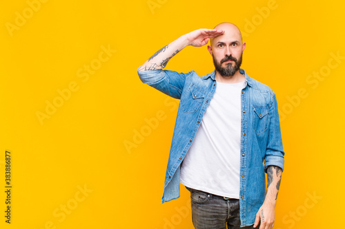 Fototapeta young bald and bearded man greeting the camera with a military salute in an act