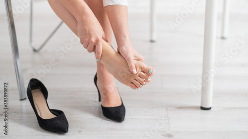 Photo A business woman sits in an office on a chair, takes off her high-heeled shoes a