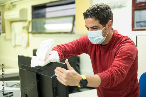 Photo computer worker disinfects his keyboard and computer before working
