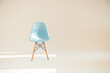 One blue chair in a light white Studio lit by sunlight in a minimalistic style with a copy of the space, selective focus