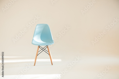 Fotografie, Obraz One blue chair in a light white Studio lit by sunlight in a minimalistic style w