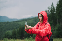 Young Female Backpacker In A Red Raincoat Jacket Is Using Her Mobile Phone And Taking Pictures, Mountain Forest On The Background.