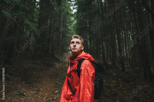 Obraz na plátně Portrait of a handsome pensive caucasian young man looking up, feeling curious and adventurous, wearing a red waterproof coat and black backpack