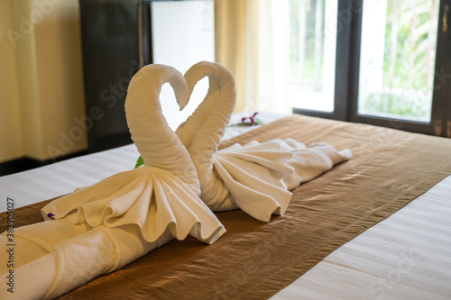 Fotografie, Obraz The white towel folded into swan shape and placed like heart shape on bed, luxur