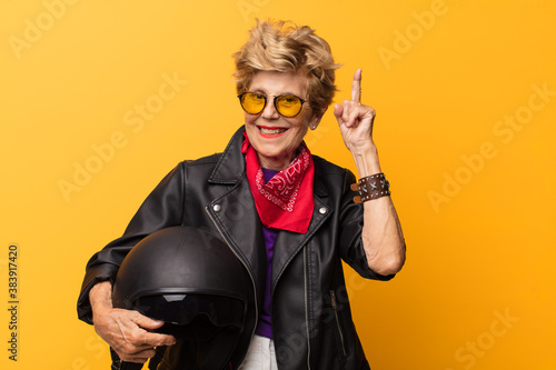 mature old beautiful woman feeling like a happy and excited genius after realizing an idea, cheerfully raising finger, eureka!. motorbike concept