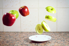 Sliced Green Apple Levitating Over A Small Plate On Marble Table And Apples Levitating