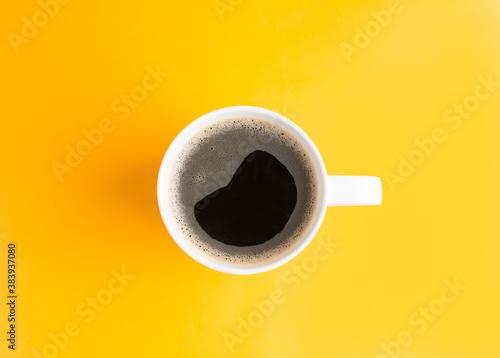 plano cenital de una taza blanca con café americano negro sobre un fondo color amarillo Wallpaper Mural