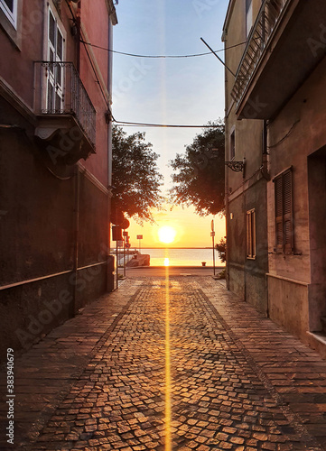 Sunset with sunbeam in an old italian street