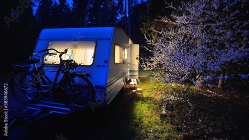 Illuminated caravan trailer on a forest road under a blooming tree in Spring at night, close-up. Transportation, vacations, weekend, road trip, home, alternative lifestyle, leisure activity, camping