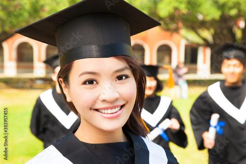 beautiful female college graduate with classmates at ceremony