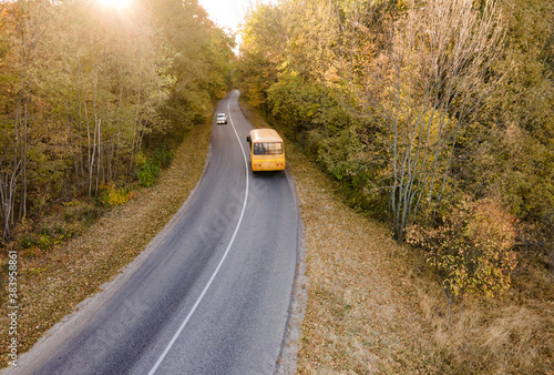 Aerial view of road with school bus in beautiful autumn forest at sunset.