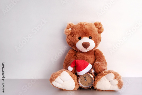 Teddy bear and alarm clock on silver background #383977423