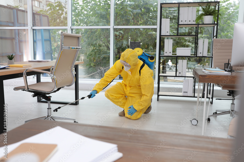 Fototapeta Janitor in protective suit disinfecting office to prevent spreading of COVID-19