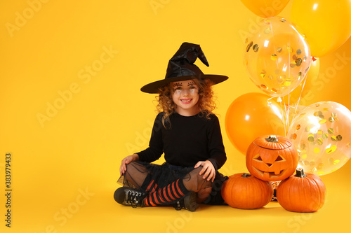 Vászonkép Cute little girl with pumpkins and balloons wearing Halloween costume on yellow