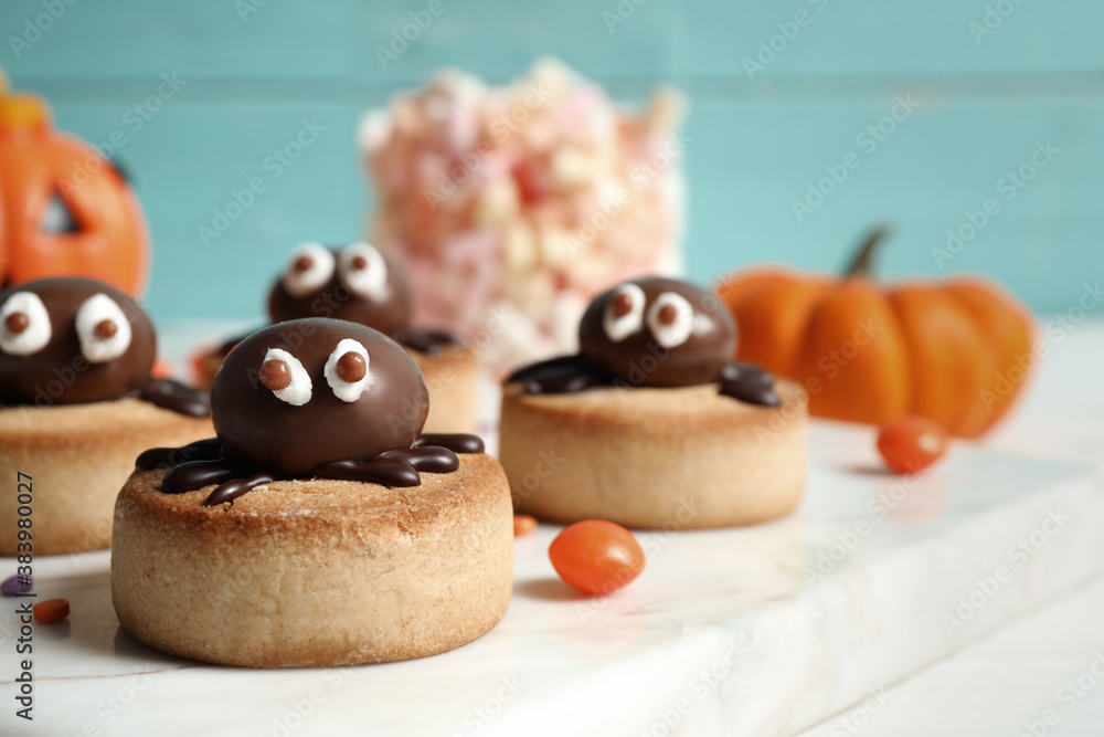 Fototapeta Delicious biscuit with chocolate spider on white table, closeup. Halloween celebration