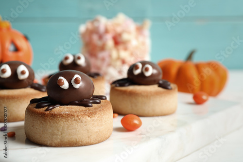 Foto Delicious biscuit with chocolate spider on white table, closeup