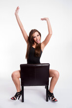 Rejoicing Young Beautiful Barefoot Woman Straddles Black Leather