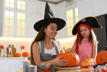 Mother And Daughter Making Pumpkin Jack O'lantern At Table In Kitchen. Halloween Celebration