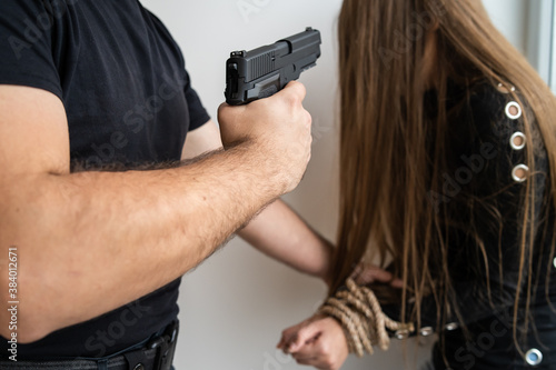 Cuadros en Lienzo Close up on hands of unknown man holding woman tied with rope pointing gun to he