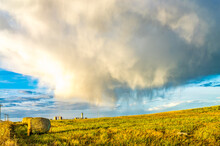 Rural Landscape In Province Of Alberta With Rain Cloud Over Harvested Hay  Field, Hay Bales And Oil Industry Maintanesce Station With Bins