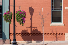Red Painted Brick Wall Texture Background Featuring Windows And A Hanging Flower Planter, With Street Light Shadows