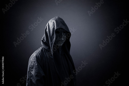 Photo Ghostly figure in hooded cloak in the dark